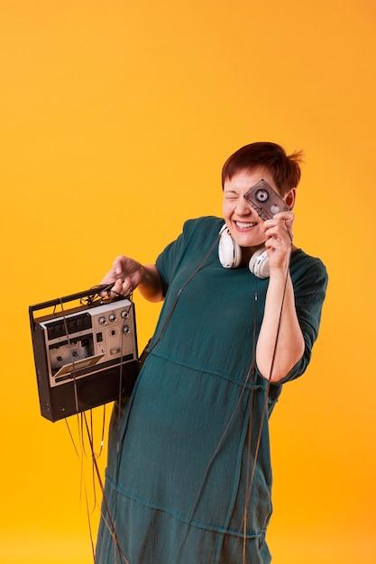 Mujer mayor divertida que sostiene un reproductor de cassette Foto gratis