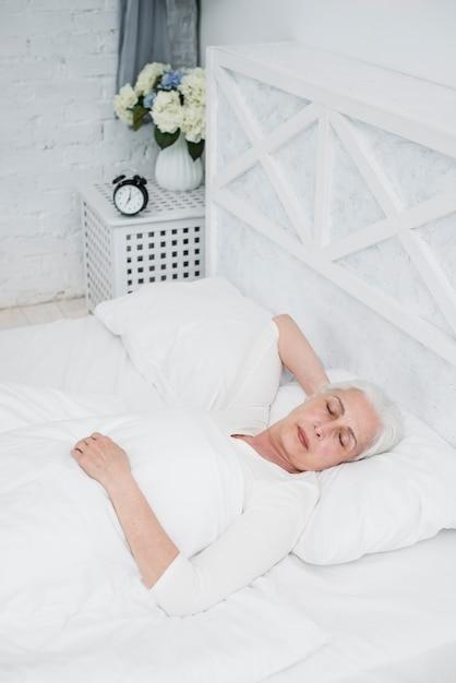 Mujer mayor durmiendo en una cama blanca Foto gratis