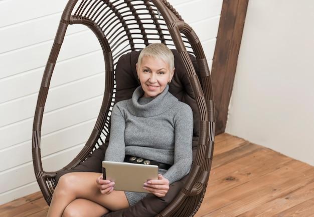Mujer mayor moderna que sostiene una tableta Foto gratis