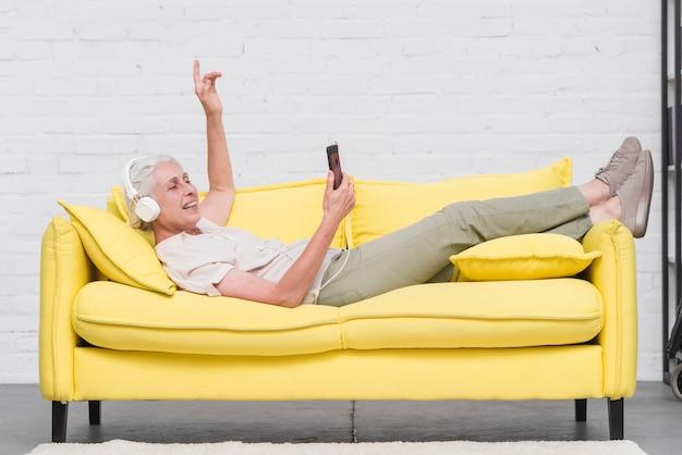 Mujer mayor que miente en el sofá amarillo que disfruta de la música en el móvil a través del auricular Foto gratis