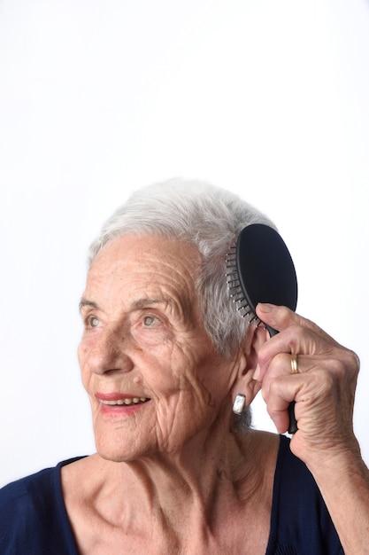 Mujer mayor que se peina el pelo en el fondo blanco Foto Premium