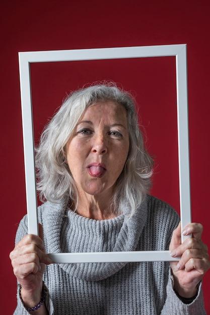 Mujer mayor que sostiene la frontera blanca del marco que se pega hacia fuera su lengua contra el contexto rojo Foto gratis