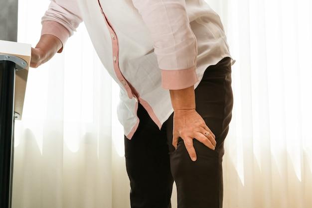 Mujer mayor que sufre de dolor de rodilla en casa, concepto de problema de salud Foto Premium