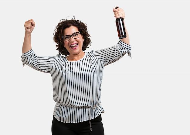 Mujer de mediana edad, feliz y divertida, sosteniendo una botella de cerveza, se siente bien después de un día intenso. Foto Premium