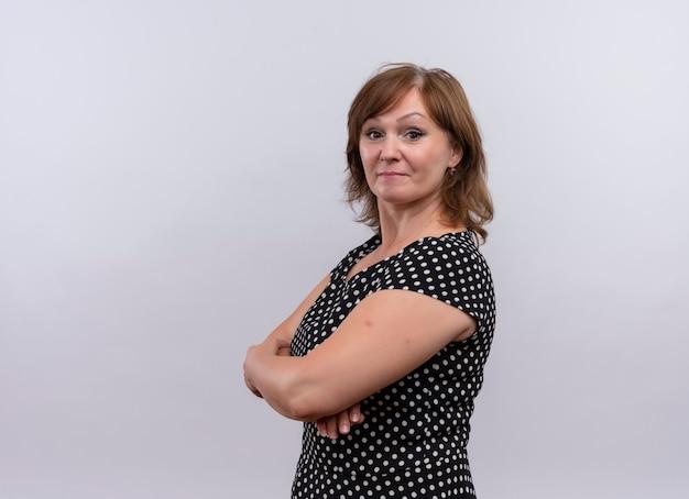 Mujer de mediana edad mirando seriamente de pie con postura cerrada en la pared blanca aislada con espacio de copia Foto gratis