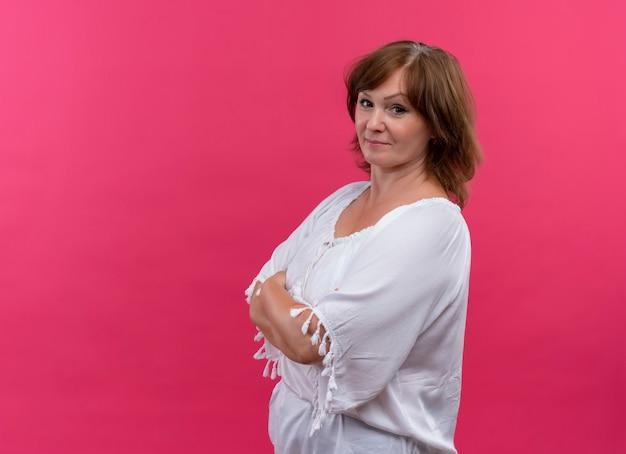Mujer de mediana edad segura de pie con postura cerrada en pared rosa aislada Foto gratis