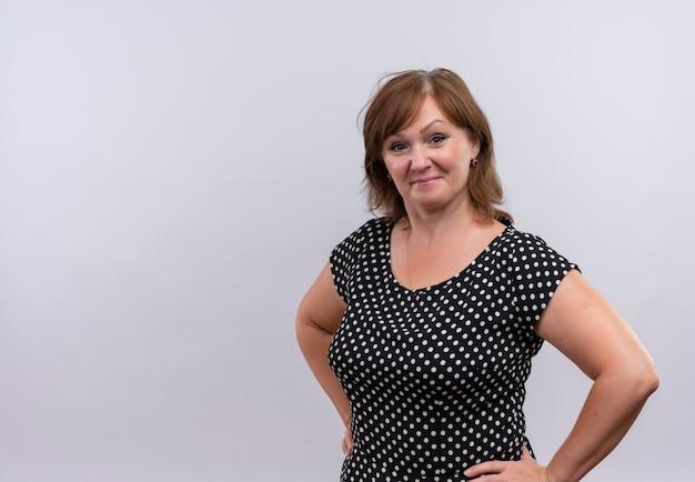 Mujer de mediana edad segura que pone las manos en la cintura en la pared blanca aislada con espacio de copia Foto gratis