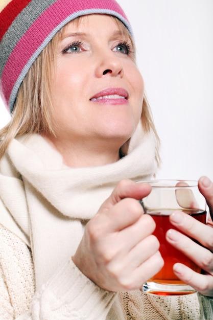 Mujer de mediana edad con té caliente vistiendo ropa de invierno sobre un fondo blanco. Foto gratis
