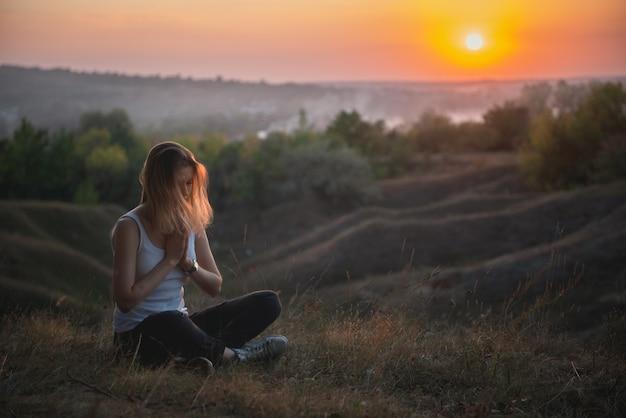 Mujer meditación o rezando al atardecer Foto Premium