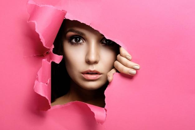 La mujer mira en el agujero de papel de color rosa, maquillaje y cosméticos de belleza de moda, salón de belleza Foto Premium