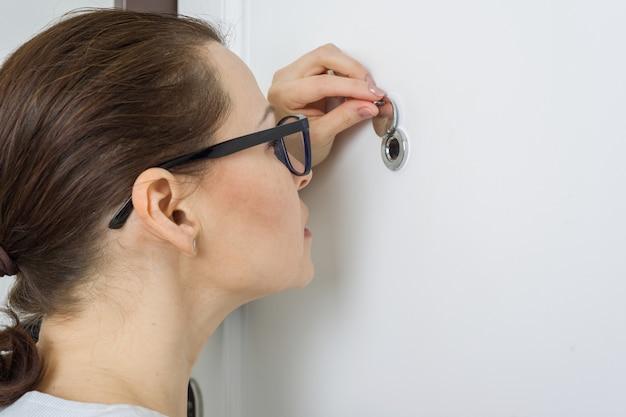 Mujer mira por la mirilla de la puerta principal del departamento Foto Premium