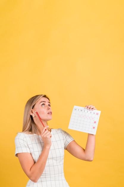 Mujer mirando hacia arriba y pensando en copia espacio Foto gratis