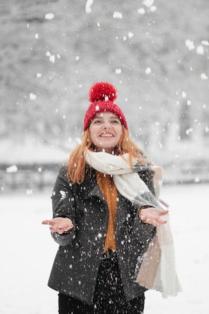Mujer mirando hacia arriba y de pie en la nieve. Foto gratis