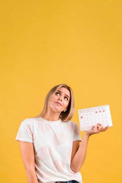 Mujer mirando hacia arriba y sosteniendo el calendario de la menstruación Foto gratis