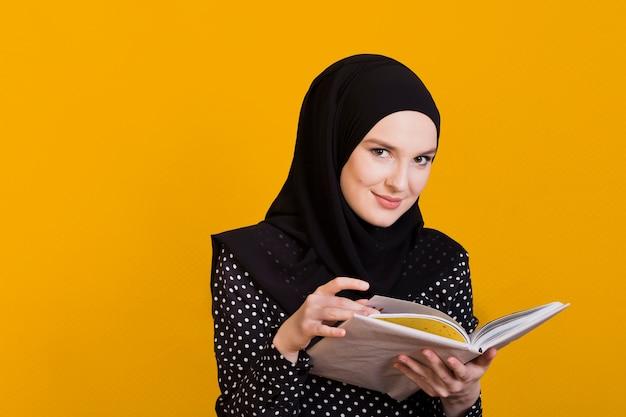 Mujer mirando a cámara con libro en mano sobre superficie Foto gratis