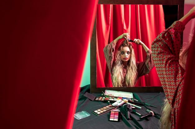 Mujer mirando en el espejo y cepillando su cabello Foto gratis