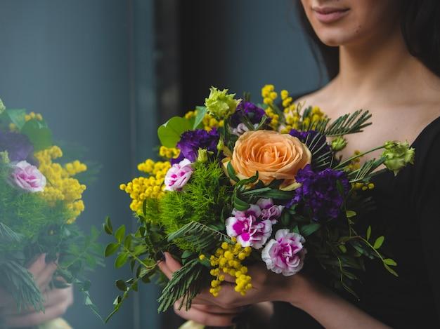 Una mujer mirando a un ramo de flores muy colorido frente a la ventana Foto gratis