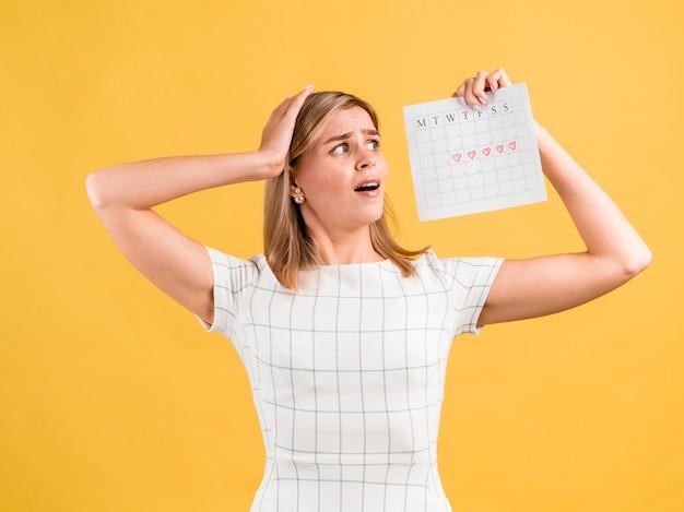 Mujer mirando su calendario de menstruación con miedo Foto gratis