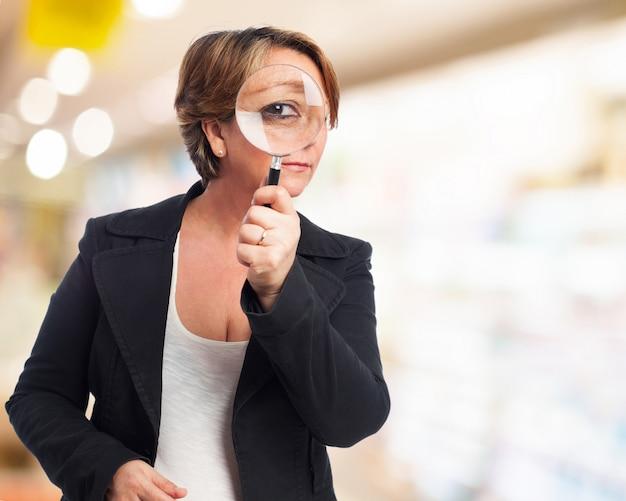 Mujer mirando a través de una lupa Foto gratis