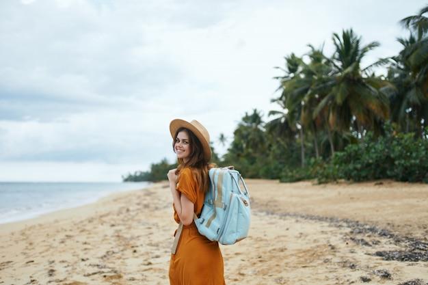 Una mujer con una mochila azul con un vestido amarillo y un sombrero camina por el océano a lo largo de la arena con palmeras Foto Premium