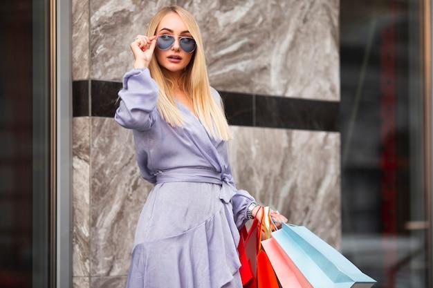 Mujer de moda de ángulo bajo en compras Foto gratis