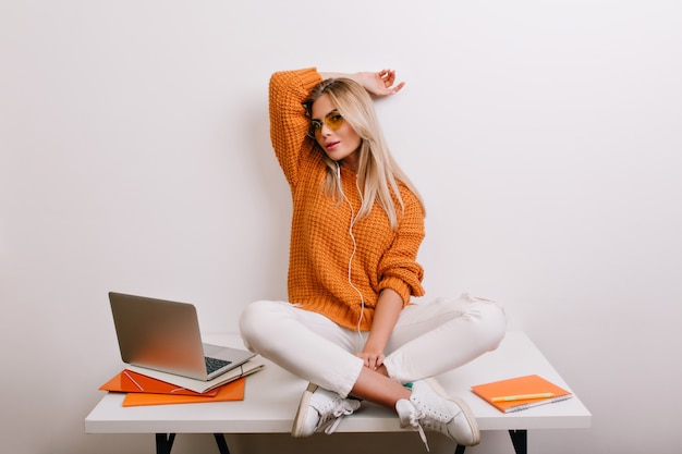 Mujer De Moda Feliz En Pantalones Blancos De Moda Jugando En La Oficina Sentada Con Las Piernas Cruzadas En La Mesa Cerca De La Computadora Foto Gratis