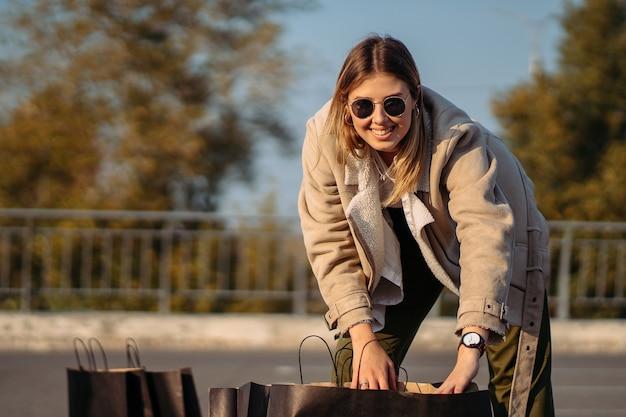 Mujer de moda joven con bolsas de la compra en el estacionamiento Foto gratis