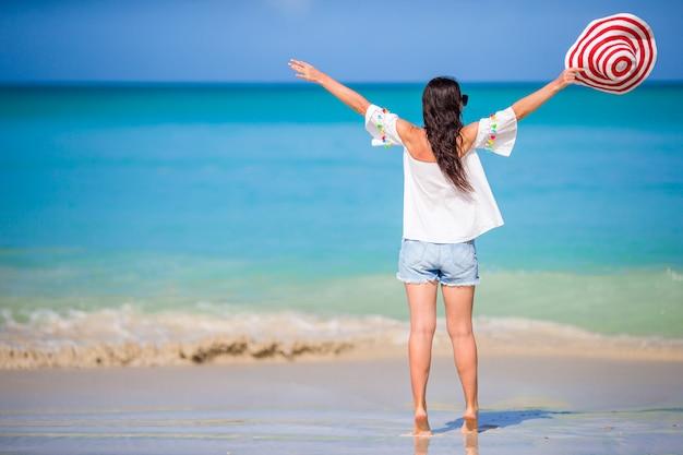Mujer de moda joven con sombrero en la playa Foto Premium