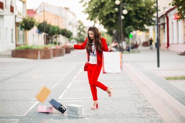 La mujer de moda en traje rojo con bolsas de compras dejó caer cajas de zapatos en la calle. Foto Premium