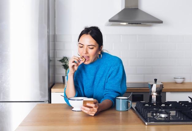 Mujer moderna desayunando en la cocina Foto gratis