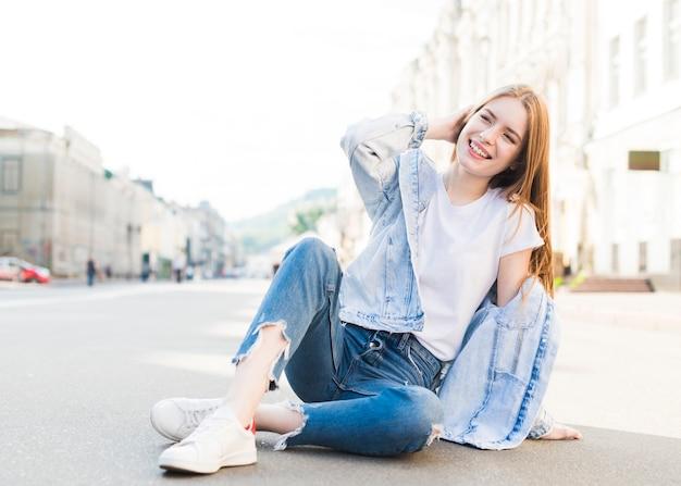 Mujer moderna joven elegante que se sienta en el camino y la presentación Foto gratis
