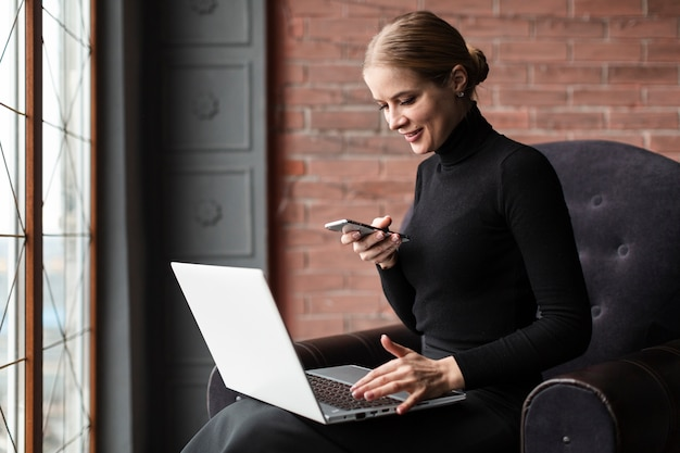 Mujer moderna sonriente que trabaja en la computadora portátil Foto gratis