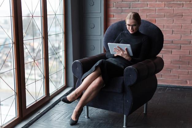 Mujer moderna con tableta en sofá Foto gratis