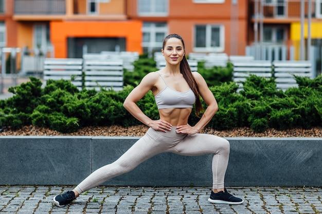 Mujer morena atlética, deportiva que hace ejercicio en cuclillas en parque soleado delante de casas urbanas. Foto Premium