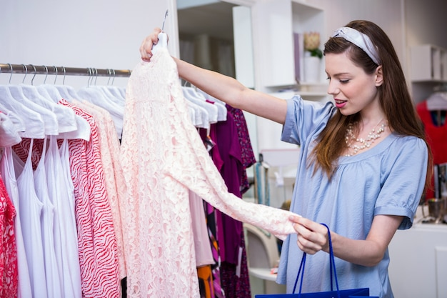 Mujer morena de compras para la ropa en boutique de moda  4e8bde6d0f71