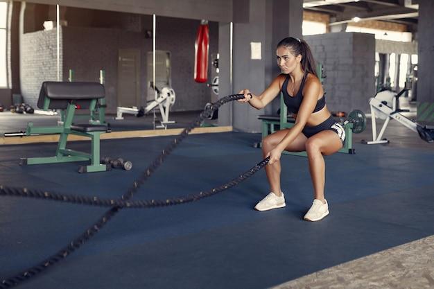 Mujer morena deportiva en un entrenamiento de ropa deportiva en un gimnasio Foto gratis