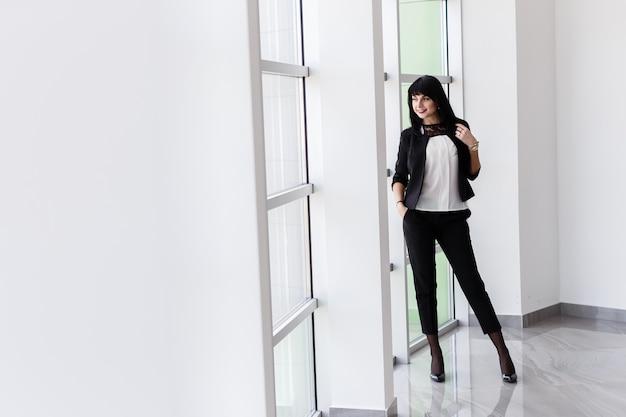 Mujer morena feliz atractiva joven con el pelo largo que se coloca cerca de la ventana en la oficina, sonriendo, mirando hacia fuera a la ventana. Foto Premium