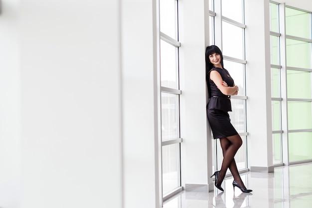La mujer morena feliz atractiva joven vestida en un traje de negocios negro con una falda corta se está colocando cerca de la ventana en la oficina, sonriendo, mirando a la cámara. Foto Premium
