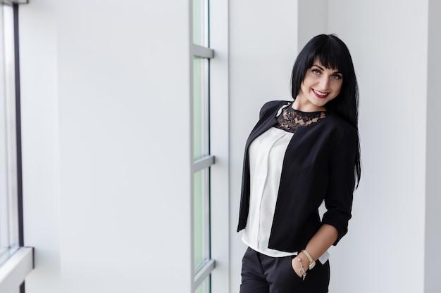 La mujer morena feliz atractiva joven se vistió en un traje de negocios negro que se colocaba cerca de la ventana en oficina, sonriendo, mirando la cámara. Foto Premium