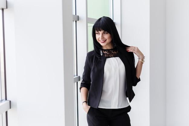 La mujer morena feliz atractiva joven se vistió en un traje de negocios negro que se colocaba cerca de la ventana en una oficina, sonriendo, mirando a la ventana. Foto Premium