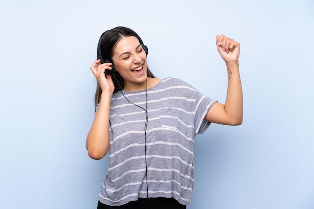 Mujer morena joven que escucha la música con los auriculares Foto Premium