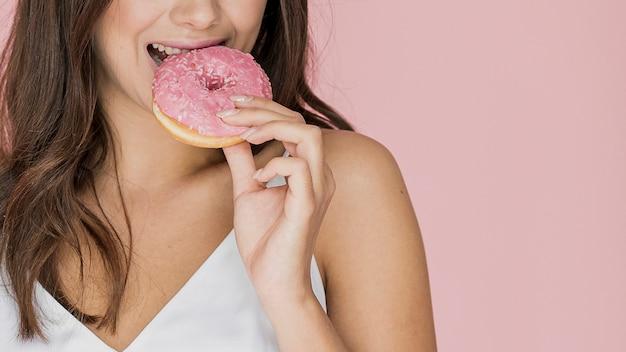 Mujer morena mordiendo un donut Foto gratis