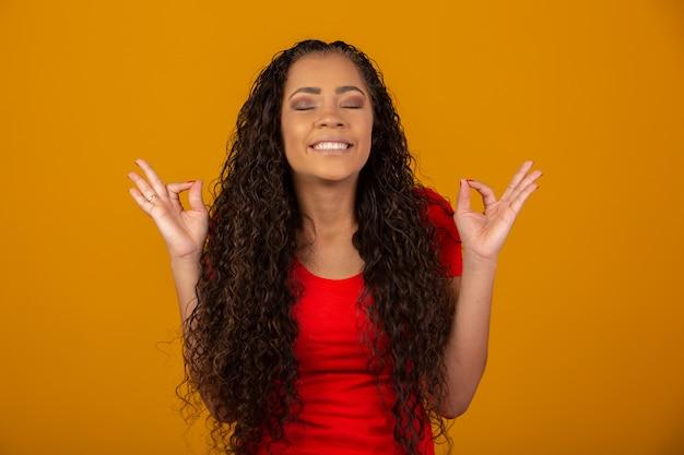 Mujer morena con pelo largo y brillante rizado rezando Foto Premium