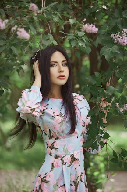 Mujer morena en las ramas de un hermoso árbol floreciente. vestido corto de verano Foto Premium