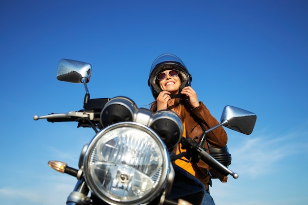 Mujer morena sexy en chaqueta de cuero poniéndose el casco y sentado en una motocicleta de estilo retro en un hermoso día soleado Foto gratis