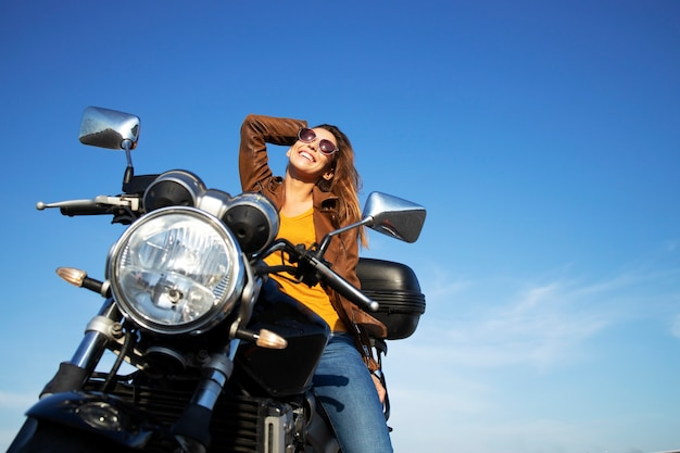 Mujer morena sexy en chaqueta de cuero sentada en una motocicleta de estilo retro en un hermoso día soleado Foto gratis
