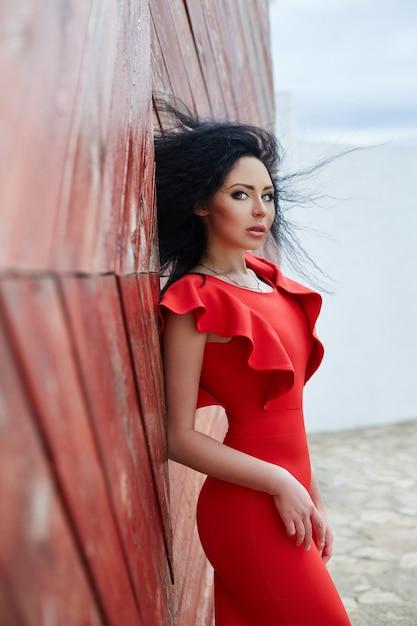 Mujer morena sexy en un vestido rojo está de pie cerca de la puerta roja. Foto Premium
