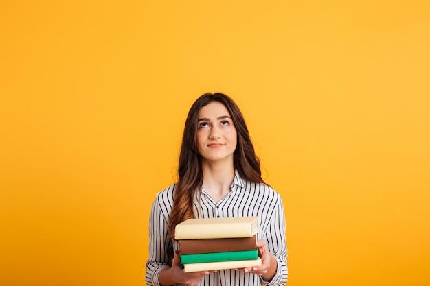 Mujer morena sonriente en camisa sosteniendo libros y mirando hacia arriba Foto gratis