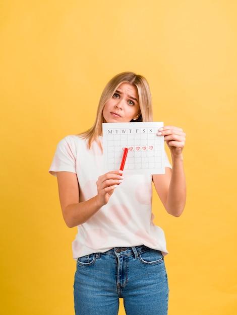 Mujer mostrando su primer día de menstruación Foto gratis