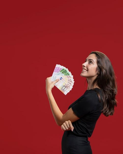 Mujer mostrando sus compras dinero con espacio de copia Foto gratis